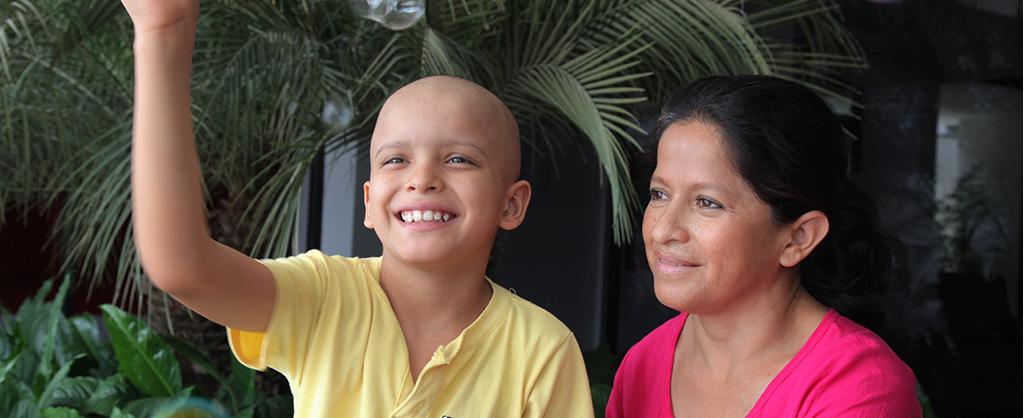 Niño calvo levantando su mano para saludar, mientras sonríe, al lado de su madre.
