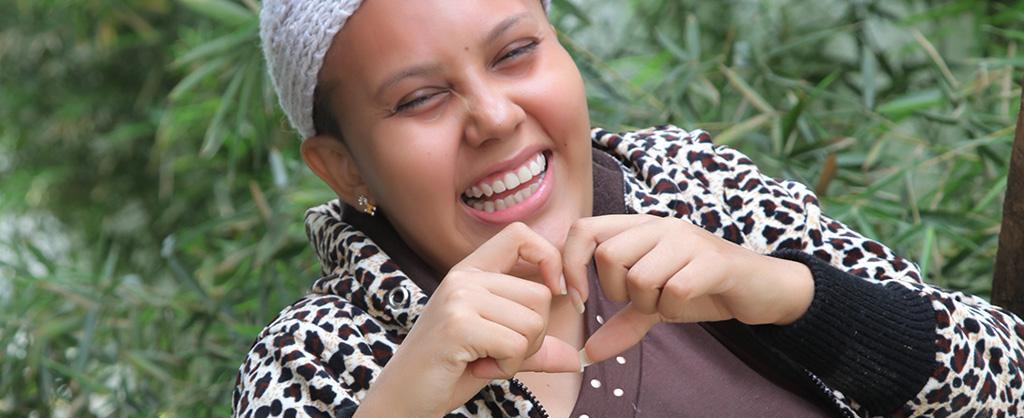 Una jovencita ríe mientras hace el símbolo de un corazón con sus manos.