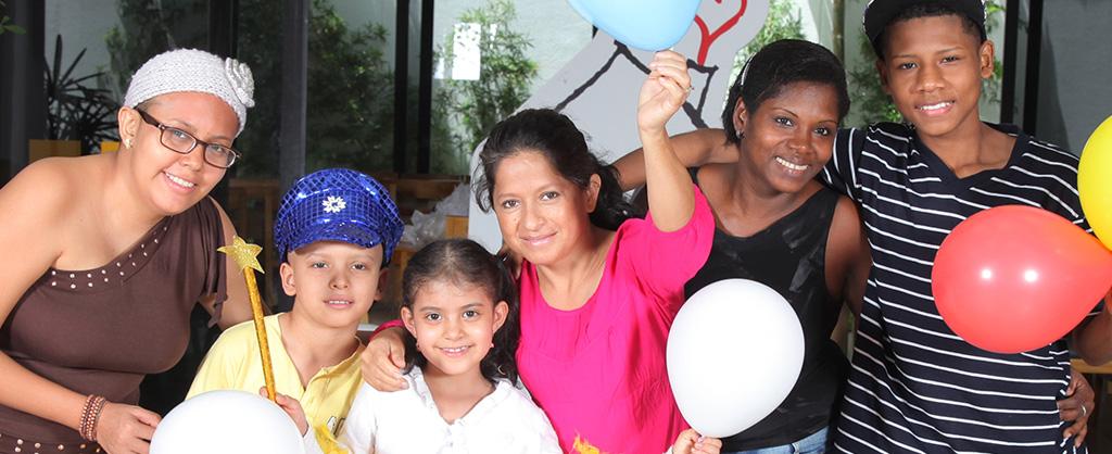 Dos familias sostienen globos de colores y sonríen.