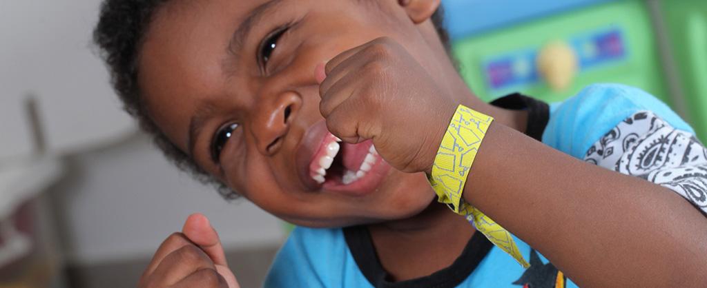 Un pequeño, con una manilla de hospital en su muñeca, ríendo a carcajadas.