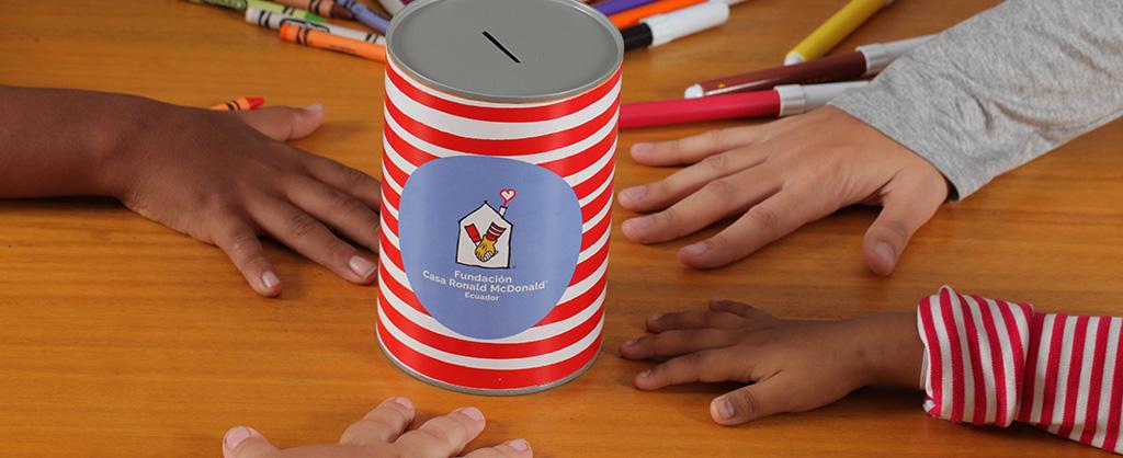 Una alcancía de recaudación de fondos para la Fundación Casa Ronald McDonald Ecuador en el centro de una mesa; alrededor se ven varias manos de niños.