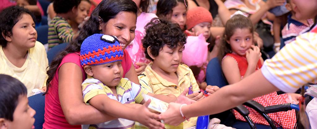 Hay varias familias reunidas en un gran salón. Se ve a una madre sosteniendo a su hijo enfermo mientras que el recibe un regalo.