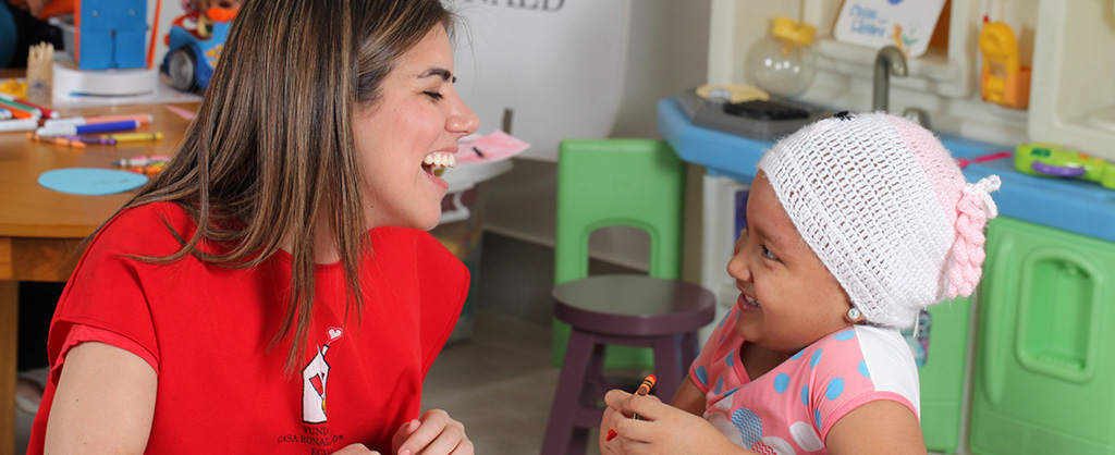 En una sala, hay una mujer, que tiene una camiseta roja con el logo de la Fundación Casa Ronald McDonald Ecuador, ríe al lado de a niña quien sostiene una crayola en su mano y dibuja.